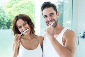 man and woman brushing teeth