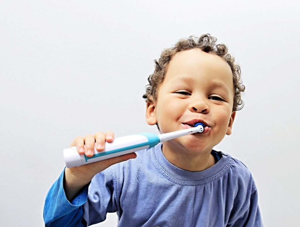 Little boy brushing his teeth at a family dentist visit
