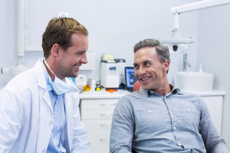 a dentist smiles as he listens to a male patient during an appointment