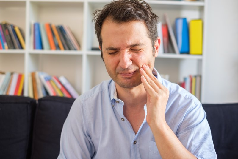 Waterbury man with gingivitis holding cheek in pain