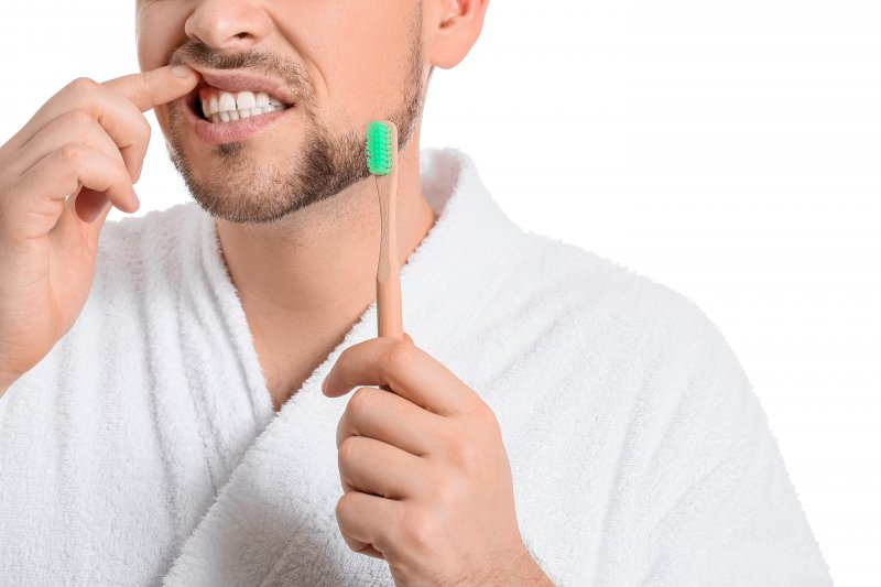 man holding toothbrush pointing to gums
